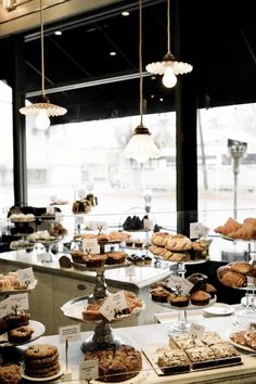 The bakery section features a selection of goods displayed on cake stands. Vintage milk glass lighting hangs above.