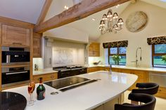 An aga, built in ovens and hobs on the island provide a multitude of cooking options