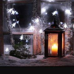 Laterne mit Kerze vor einem alten Fenster