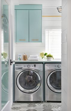 Gorgeous laundry room with stainless washer and dryer plus soft turquoise cabinetry