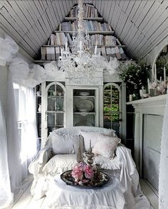 close up of magic doll house cottage with white interior, crystal chandelier, bookcase, cozy