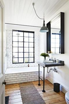 Light and airy bathroom. The slim silhouette of the vanity and the 24 pane glass window are stunning.