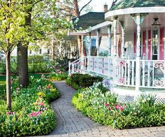 If you have a front porch, add a skirt of colorful flowers. Even a tiny pocket planting such as the one shown here offers big color and interest in the front yard. Mix annuals with perennials and bulbs -- and a dwarf evergreen or two -- so you can enjoy the show all year long.