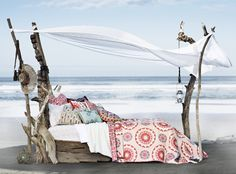 Driftwood daybed on the beach. Makeshift canopy and red and aqua bedding
