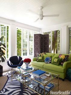 """Another view of the sunroom: Adler's needlepoint Love pillow (""""I believe in infantile, happy emblems"""") and his green concentric-squares pillows keep company with Josef Frank's Hawaii Brown pillows on the sofa. Arne Jacobsen Swan chair from Design Within Reach."""