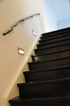 http://www.living-classics.de Black and white staircase. Black painted stairs, stair lighting, handrail made of a branch