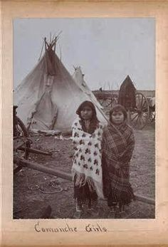Two Comanche Indian girls taken outside of their tipi in Texas around 1900