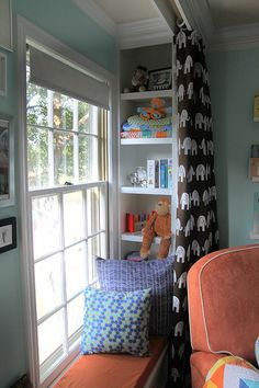 I love bookshelves flanking a window, with the curtains hanging from the ceiling in front of the bookshelf.  This picture also incorporates horizontal shelving as a window seat, but can definitely face bookshelves outward (into the room) and omit the window seat.  Cool way to get extra storage without adding visual clutter.
