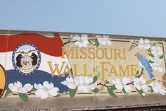 The Missouri Wall of Fame was conceptualized by the now defunct River Heritage Mural Association and completed in 1995. Local artist Margaret Dement designed the mural, drawing figures of famous Missouri faces who were either born in Missouri or achieved fame while living in the state, including Harry Truman, George Washington Carver, outlaws Frank and Jesse James, and author Mark Twain. The drawings were projected onto the wall and traced by Weatherford Sign Company.