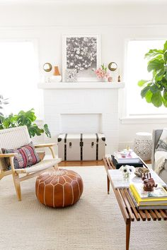 bright white living room with flower print above fireplace