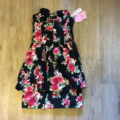 Girly floral dress strapless with peplum Black peplum dress with red roses. Cute bow on the chest. Size small. 100%. Cotton. No zipper. Never worn. NWT. Dresses Mini