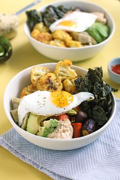 ***** //// A roasted veggie rainbow protein power bowl topped with a fried sunny sided up egg and hummus for dipping.