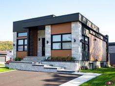 Réalisation contemporaine d'inspiration cubique avec entrée à paliers. Modèle personnalisé conçu pour respecter le style architectural du quartier et l'inclinaison du terrain.