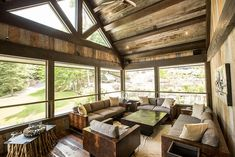 Unique coffee tables crafted from twigs steals the show in this rustic cabin sunroom [Design: Gilbert + Burke]