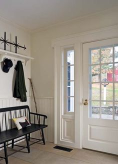 In the mudroom, Murray incorporated beadboard, shelving, and dog-eared molding around the door to keep the look simple. Deacons Bench, Greek Revival Architecture, Entry Foyer, Entrance Hall, Style Deco, Back Doors, Exterior Doors, Decoration, House Plans