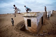 Mauritania. children at play. As a child I too leapt from similar structures- a WWII gun emplacement. Wot larks!