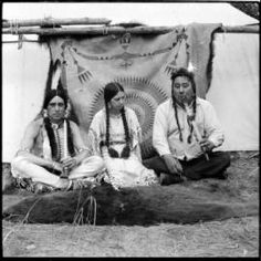 1930 photo of two American Indian men with pipes sitting next to Indian woman at Crow Fair.  Photo by Charles Belden
