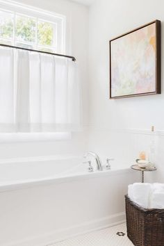 Alyssa Rosenheck - Julie Couch Interiors - Chic bathroom boasts a drop-in tub placed under windows dressed in white cafe curtains as well as a piece of pastel colored abstract art. Bathroom Window Curtains, Bathroom Window Treatments, Bathroom Windows, Cafe Curtains, White Curtains, Hanging Curtains, Bath Window, Roman Curtains, Patterned Curtains