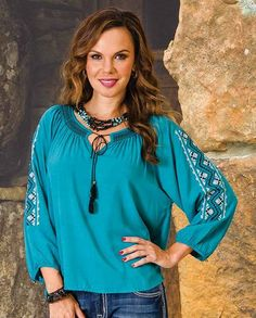 Rock & Roll Cowgirl Turquoise Aztec Peasant Top This colorful top evokes a simpler time. It boasts blue and white Aztec embroidery on the loose fit three-quarter length sleeves with elastic cuffs. A pretty gathered keyhole neckline with a black tie with tasselled ends gives is a romantic appeal.  | gifts for women ladies casual clothing for ladies cold weather winter layering basics essentials Casual Outfits for women Country Chic #countrygirl #CountryFashion #countryoutfit drysdales.com