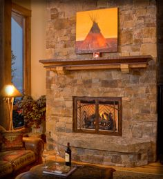 Rustic living room with rock fireplace surround and wrought iron mantel with wood accent, and iron fireplace door