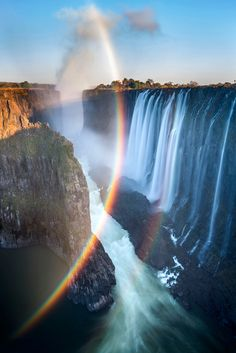 Spray rainbow over Victoria Falls at sunrise, Mosi-oa-Tunya National Park, Zambia.