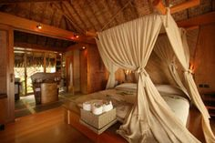 """Le Taha's Resort & Spa villas are built in the pure Polynesian tradition, exquisitely blending thatched pandanus roofs, bamboo, exotic woods, stones, corals, Marquesan """"tapa"""" cloths, and woven coconut """"nape"""" ropes."""