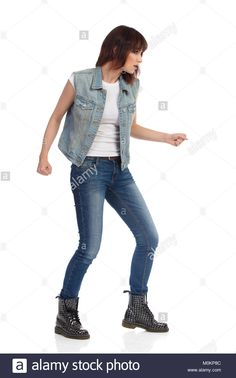 Download this stock image: Young woman in jeans vest and black boots is sneaking and looking away. Profile view. Full length studio shot isolated on white. - M0KP8C from Alamy's library of millions of high resolution stock photos, illustrations and vectors.