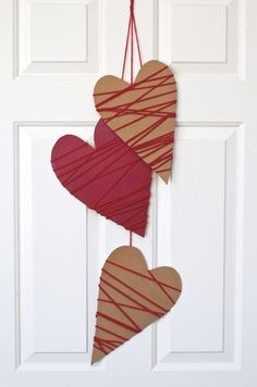 This darling door garland is made of recycled cereal boxes! We cut three tall, skinny heart shapes out of the front and back panels of two cereal boxes. Because this project should have a rustic feel, the hearts do not need to be perfect. Freehand it! Paint one or two hearts red or just leave them plain. Once dry, wrap each heart with yarn, securing in back with tape as needed. Tape a long strand of yarn to the backside of each heart then tie the top ends together in a loop for hanging.