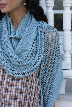 A long, shallow crescent shawl can double as a scarf, gently shaped to curve around your neck and shoulders. Easy garter stitch knitting gets a lift with a simple lace rib stitch pattern.