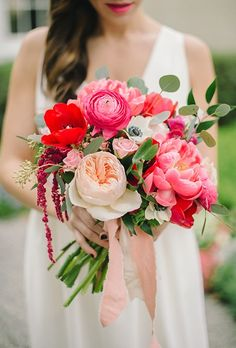 A pink and red bouquet comprised of peonies, garden roses, ranunculus, tulips, anemones, and eucalyptus, created by Blush & Vine.