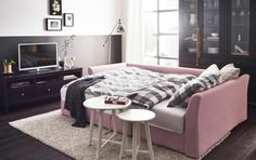A living room with a light pink corner sofa-bed made with gray/white bed linen and two white nest of tables. Combined with a black-brown TV bench and glass-door cabinets.