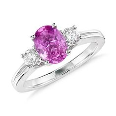 This vibrantly-hued ring features an oval pink sapphire prong-set in 18k white gold and accented with two round diamonds.