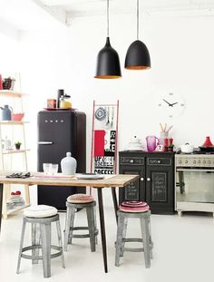 Eclectic kitchen combining classic elements, with a black smug fridge, industrial furniture & lighting