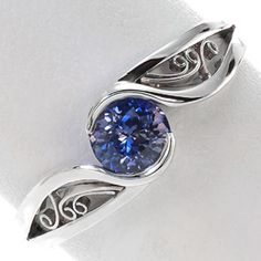 This mesmerizing solitaire design focuses on the luscious 0.80 carat round cut blue sapphire center. The band is a unique split shank with lots of movement and the ends flow around the center stone to form a half bezel setting.  #engagement #wedding #ring www.knoxjewelers.biz