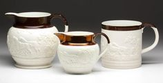 "ENGLISH CERAMIC ARTICLES, LOT OF THREE,  comprising one straight-sided mug and one jug, both being a dry body with smear glaze and brown enamel on rim, and one jug with applied glaze and gold lustre at rim, all having the same sprig mold design with hunting scene and horses. Mug and large jug marked ""T&J Hollins"" on base, otherwise unmarked. Staffordshire and other areas."