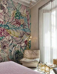 papier peint trompe l'oeil dans une chambre d'adulte, grandes fleurs et feuilles en couleurs vives, grand fauteuil faux cuir en couleur beige, petite table basse en verre blanc et des pieds en métal bronze, plafond avec des poutres blanches et luminaires suspendus en forme d'ampoules