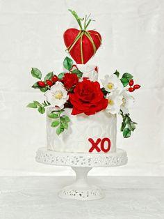 """foto Maria Francesca Ferraina Per un dolce """"Ti Amo"""" con i fiori. Rivestite di pasta di zucchero 3 torte: la base (20 cm) bianca, la centrale (15 cm) rossa, la superiore (10 cm) bianca. Avvolgere in pasta di zucchero rossa un cuore in polistirolo (12 cm). Infilate un bastoncino e spennellate..."""