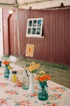 Vintage table cloths, mason jars and milk vases made for inexpensive wedding decor.