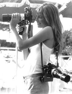 Jane Birkin with a couple of very well appointed Nikon F cameras. Plain prisms, long lenses and motor drives. And a trigger grip no less!  aconversationoncool:    Trigger happy.