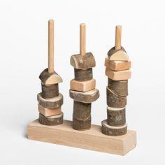 Torre de peces de fusta amb escorça, de formes i mides diverses i perforades, per encaixar en tres pals.