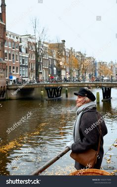 Young woman stands on the bridge and looks at the canal of Amsterdam, Netherlands.
