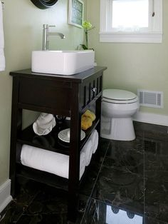 This furniture-style vanity, finished with a rich black stain and outfitted with a stylish vessel sink, fits snugly in this narrow bathroom. The open shelves below the countertop offer storage for towels and bathroom essentials while also helping the tight space feel less cramped. An upper drawer stores items best kept hidden.