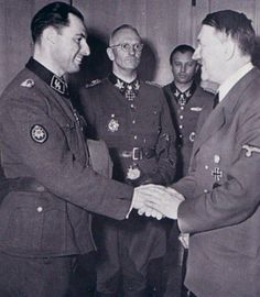 "After mighty Battle Cherkassy. February 20, 1944. From left to right: SS-Hauptsturmführer Léon Degrelle (Führer 5.SS-Freiwilligen Sturmbrigade ""Wallonien""), SS-und Generalleutnant der Gruppenführer Waffen-SS Herbert Otto Gille (Kommandeur 5. SS-Panzer-Division ""Wiking""), Adolf Hitler, SS-Brigadeführer Hermann Fegelein (Verbindungsoffizier der Waffen-SS zoom Führerhauptquartier)"
