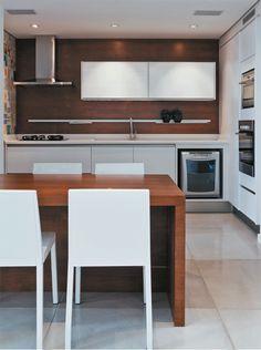 Cozinha com armários brancos e parede em tom de madeira #kitchen #cozinhamoderna #cuisine #homedecor #interiordesign #cocina