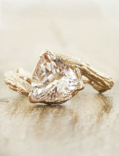 A nature-inspired engagement ring with a hand-engraved design that mimics texture of bark of a beautiful Sequoia tree in rose gold. The center stone is a wondrous and rare trillion cut pink morganite gemstone. by Ken & Dana Design.