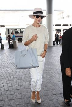 Rosie Huntington-Whiteley wears a neutral sweater, cuffed white jeans, blue gray Balenciaga tote bag, fedora, sunglasses, and suede pumps