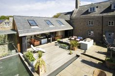 Traditional Guernsey farmhouse with contemporary Kitchen/Dining extension. Sliding folding doors, Outdoor space, Granite, Slate