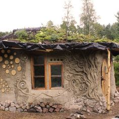 This is Heidi's beautiful roundhouse in Finland. It has an earthbag stem wall with a birch bark damp proof membrane to protect the straw bale wall on the north side of the house and cob walls on stone on the south side. The green roof is supported by round timbers that interlock in a self supporting ring. It's known as a reciprocal roof. Heidi first started making sketches of her home and then a clay model. What you see in this picture is her work this summer with her family and friends.