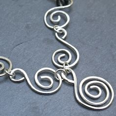 Handcrafted hammered sterling silver elements suspended from a leather necklace.