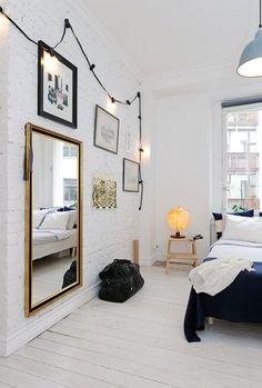 Sur ce fond de briques blanches, la guirlande Bella Vista de Seletti illumine la chambre et encadre bien tout ce qui y est exposé.